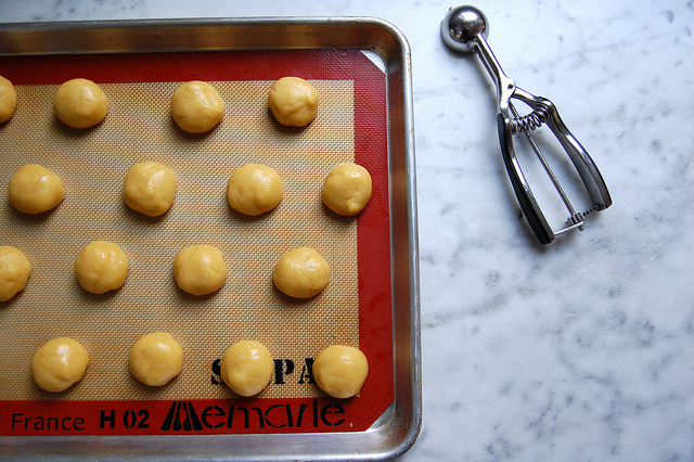 round vanilla cookies on baking sheet with scoop