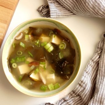 miso soup in bowl with napkin and cutting board scallions