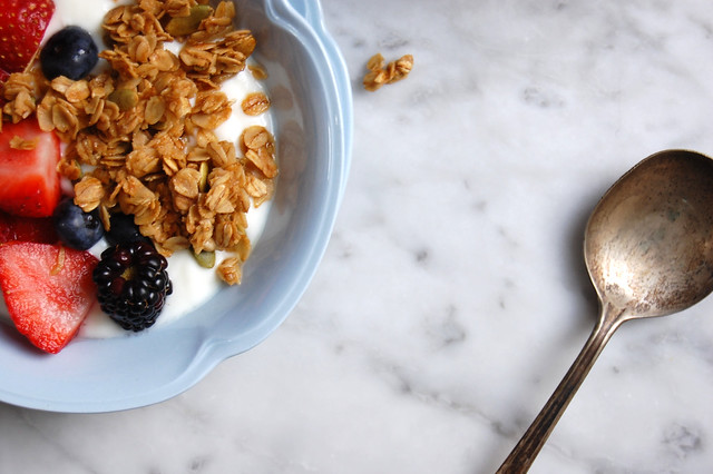 Honey Maple Granola with yogurt and fruit in blue bowl with spoon