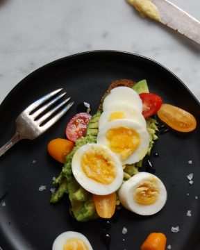 egg and avocado toast on black plate with marble counter