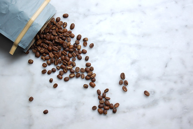 spilled coffee beans in blue bag on marble