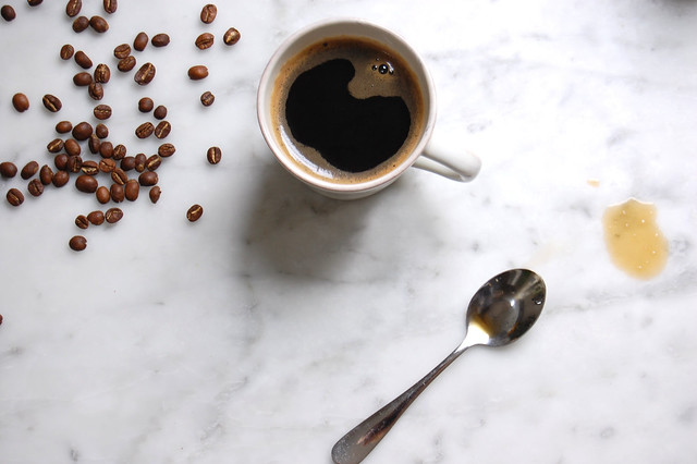 Coffee mug and spoon with spilled coffee beans on marble counter