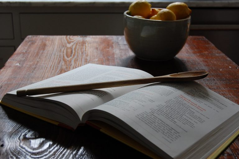cookbook with wooden spoon and bowl of lemons