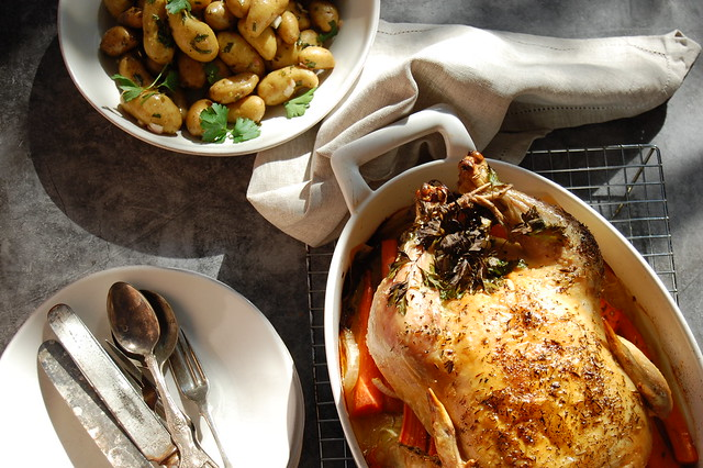 roast chicken with herbs in casserole with potatoes and linen napkin