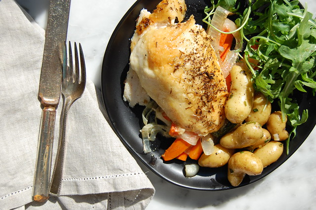 roast chicken with vegetables on plate with antique fork and knife