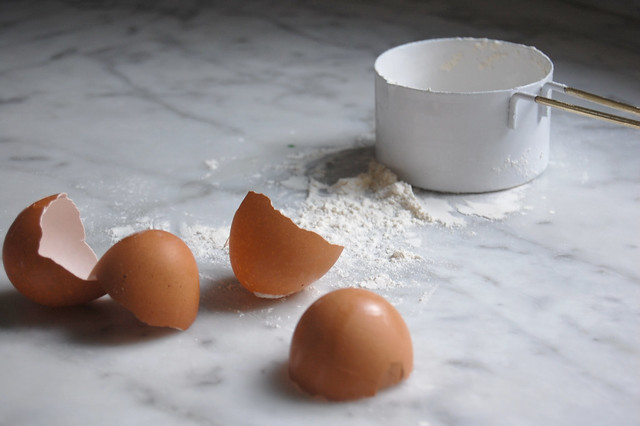 egg shells on marble counter with measuring cup