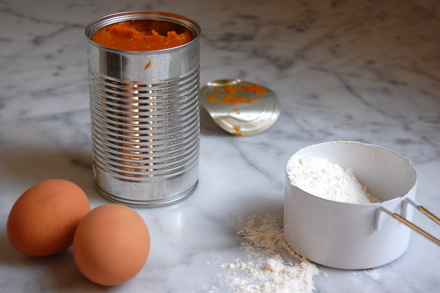 canned pumpkin with eggs and flour on marble