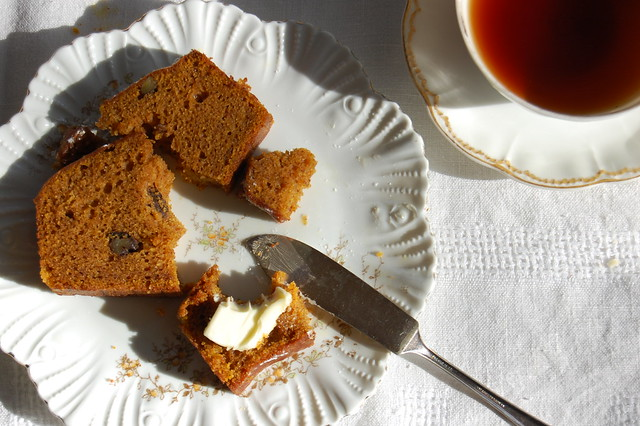 slice of pumpkin bread on china dish with tea
