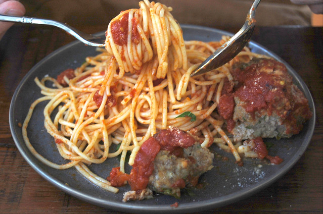 spaghetti and meatballs on black plate