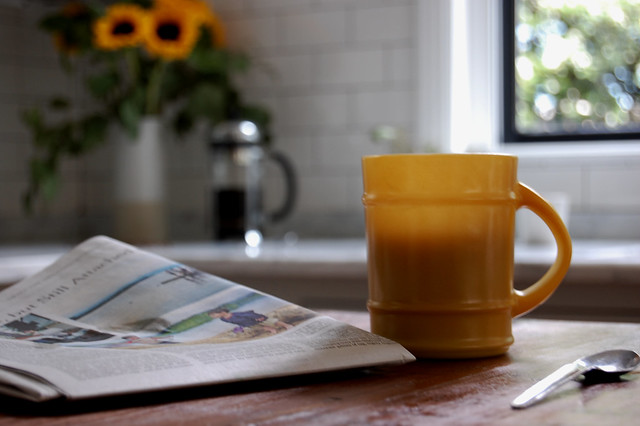 coffee in yellow mug with newspaper and sunflowers in background