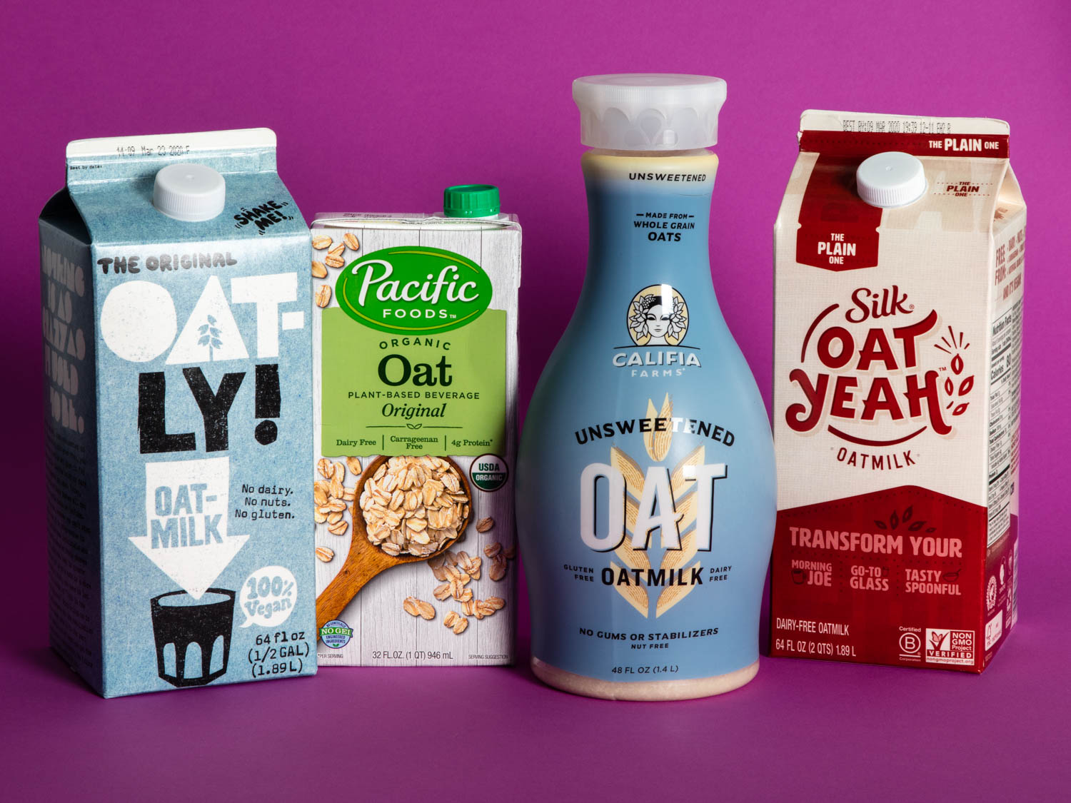 Four oat milk containers against purple background.