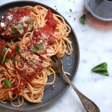 spagnetti and meatballs on dish with red wine