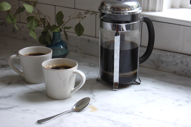 coffee mugs and French press coffee on marble countertop