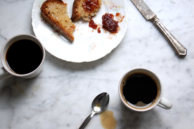 cups of coffee with toast and jam on marble countertop