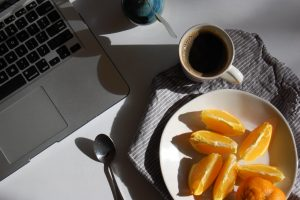laptop with orange slices and coffee
