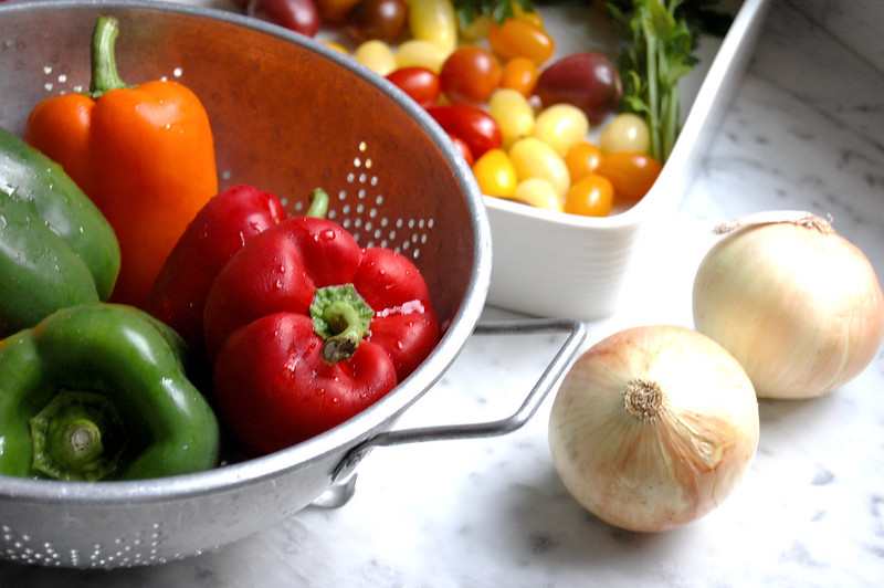 colander of peppers with tomatoes and onions
