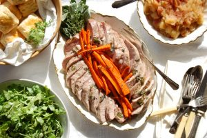 pork tenderloin sliced on platter with carrots