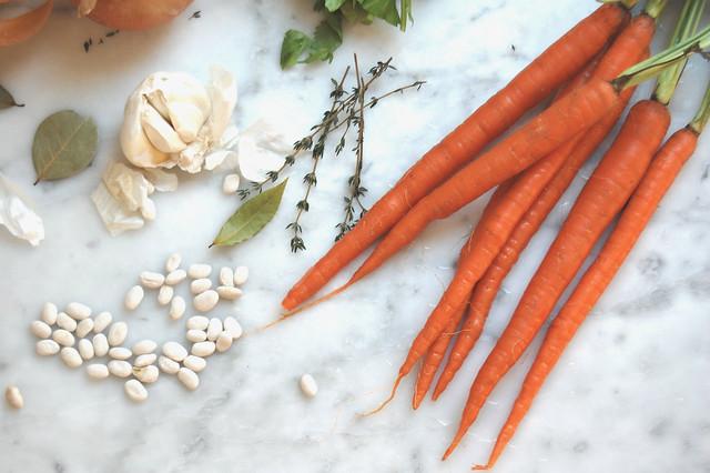 white bean soup pasta e fagioli ingredients carrots beans garlic herbs on marble coronavirus quarantine eat well