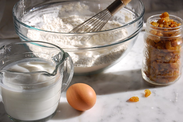 flour milk and egg with whisk on marble