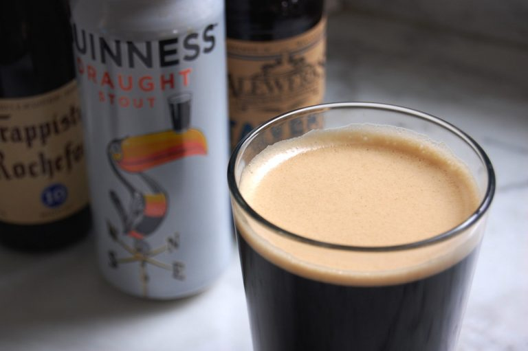 poured pint of guinness with beer in background