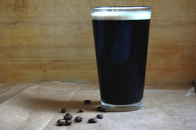 pint of stout with wood background and coffee beans