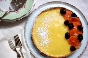 lemon tart with fruit on table with china