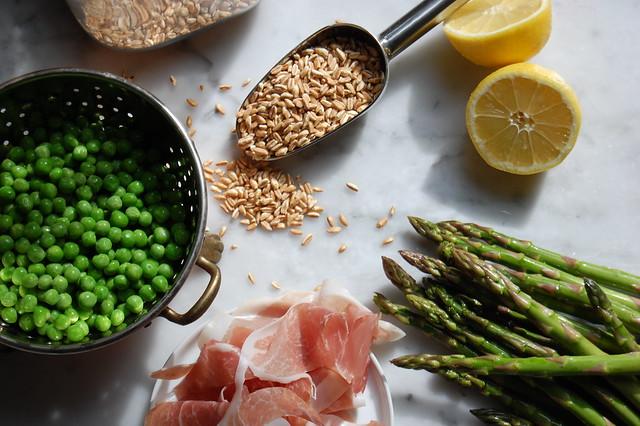 spring farro salad ingredients with peas, asparagus, ham, and lemon spring vegetables