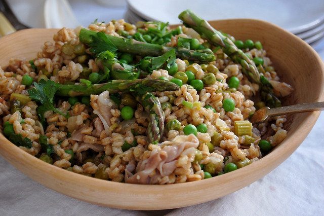 farro with spring vegetables asparagus and peas in wooden bowl