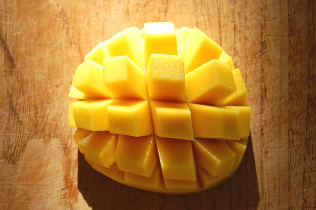 sliced mango on wooden board