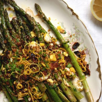 asparagus crumbled egg crumbled bacon chives on marble