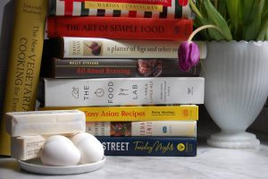 cookbooks in stack with tulips and eggs