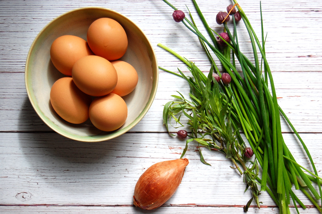 hard-boiled eggs shallot and chives on wooden board