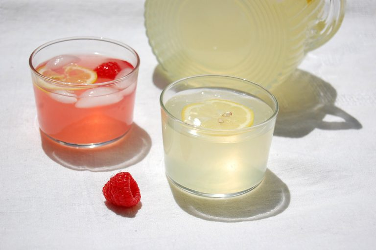 plain and pink fresh lemonade in glasses with pitcher