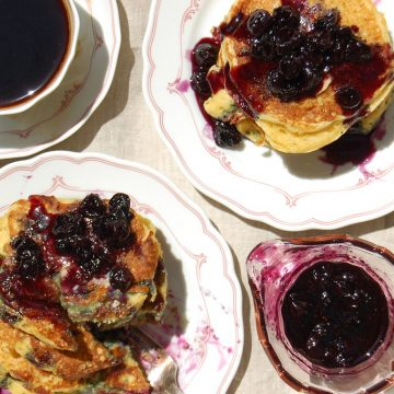 stack of cornmeal pancakes with blueberries and coffee
