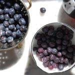 fresh blueberries in colander and pot