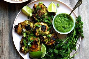 grilled chicken with green sauce and limes