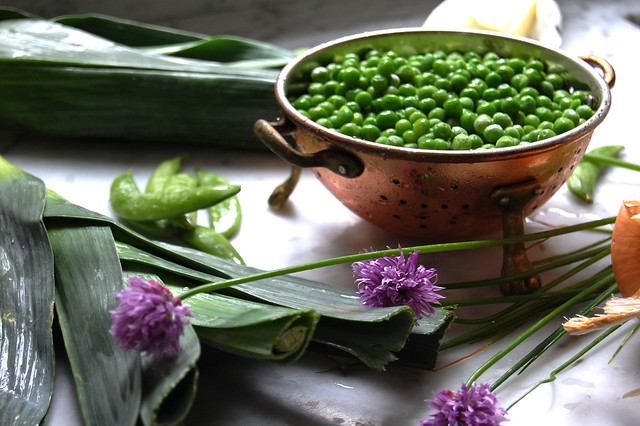 peas in colander with chive blossoms and leeks