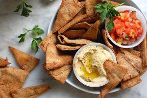 platter of homemade pita chips with salsa and hummus