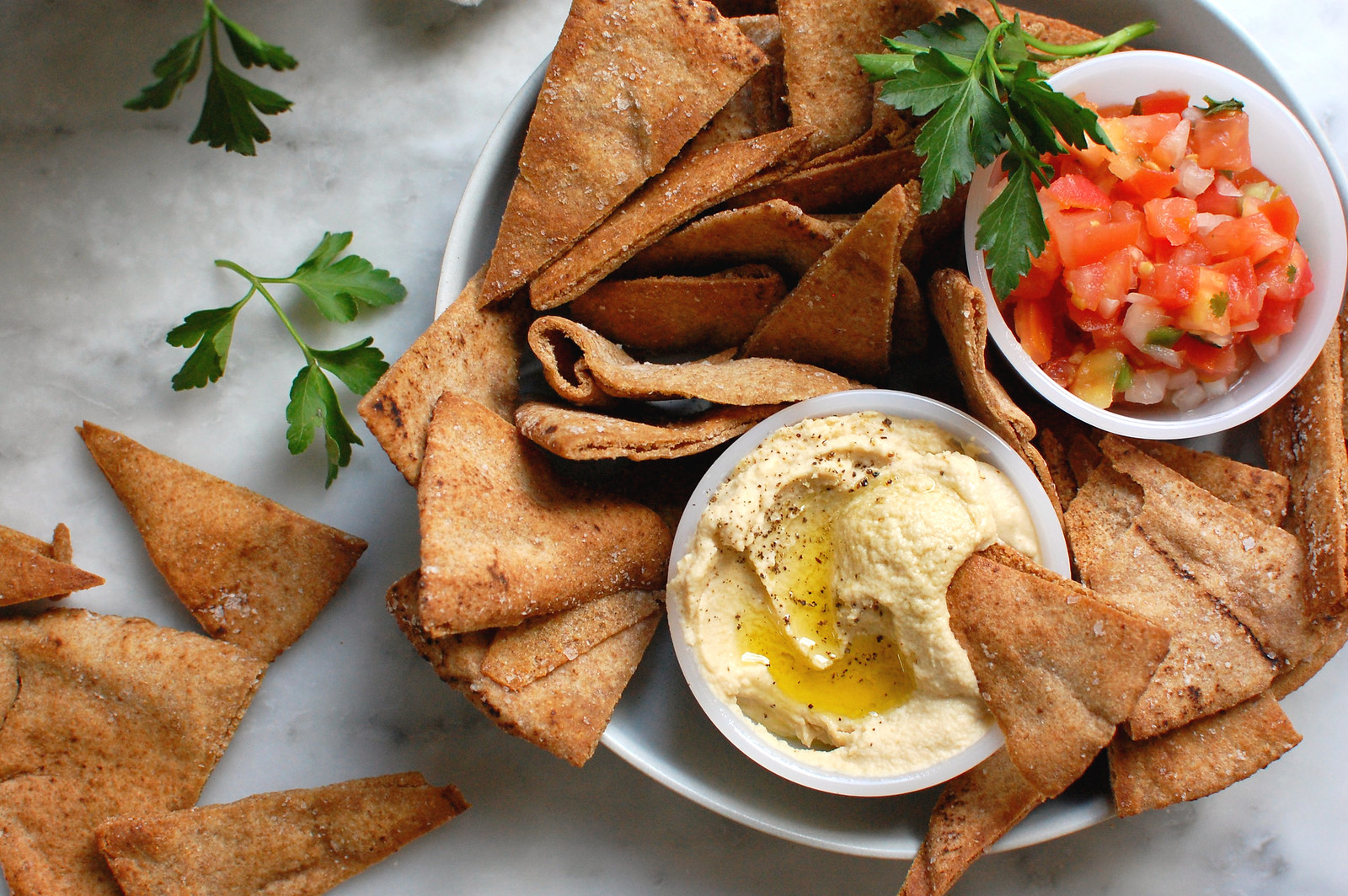 platter of homemade Stacy's pita chips with salsa and hummus