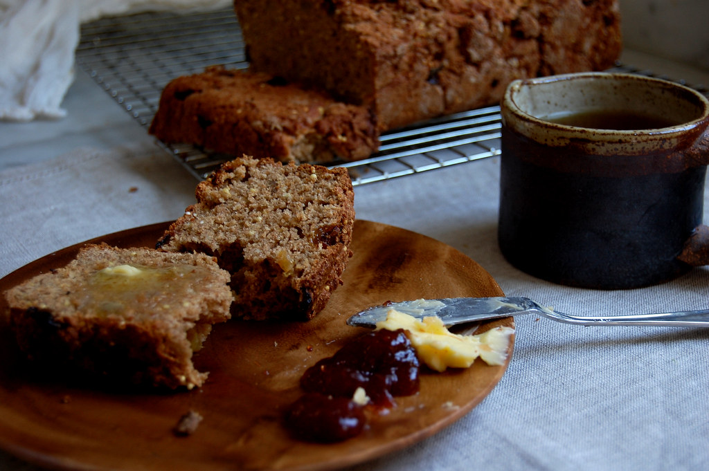 brown soda bread on cooling rack with slice on wooden plate and tea