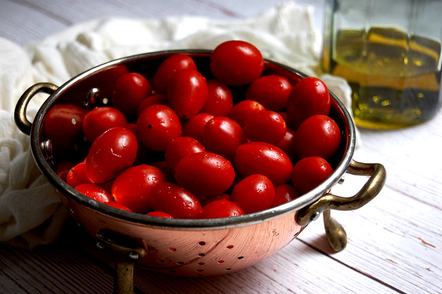copper strainer with grape tomatoes and olive oil