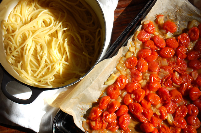 pot of spaghetti with cooked grape tomatoes on sheet pan