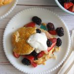 berry shortcakes on white plate topped with whipped cream