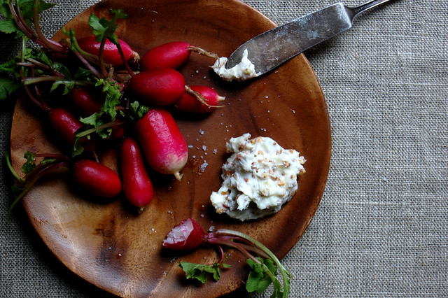 radishes with buckwheat butter on wooden plate
