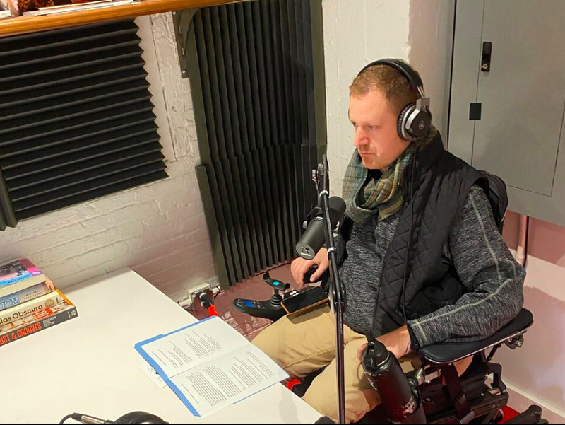 Chef Eli Kulp in podcast booth with microphone and laptop