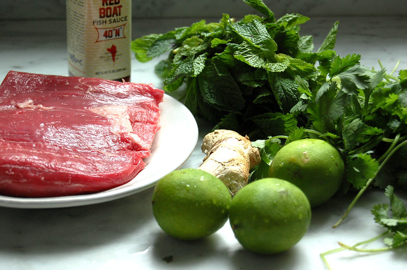 raw flank steak with limes, ginger, and herbs on marble