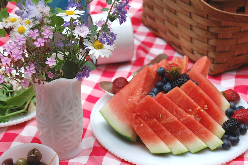 sliced watermelon on dish with picnic blanket and flowers