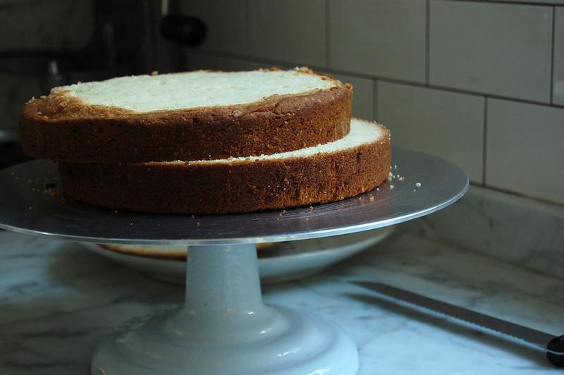 vanilla cake sliced in half on cake plate