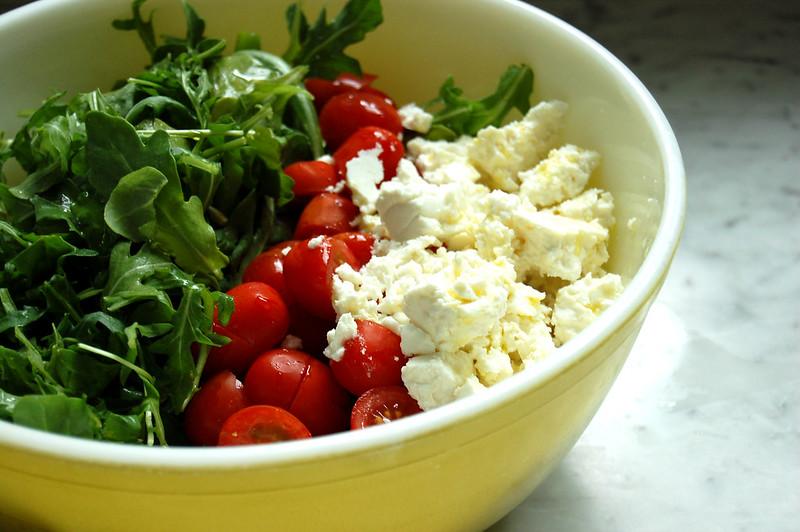 bowl of feta tomatoes and arugula