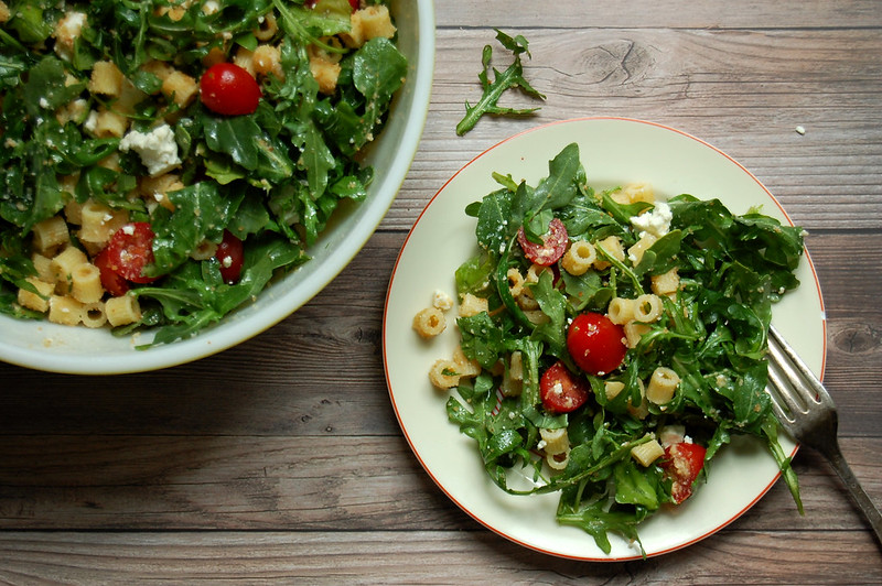 green salad with tomato pasta and feta on plate with salad bowl